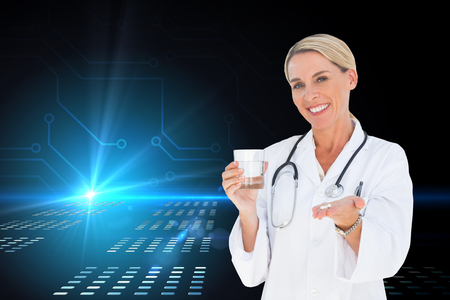 Composite image of happy doctor holding out pills and water glass photo
