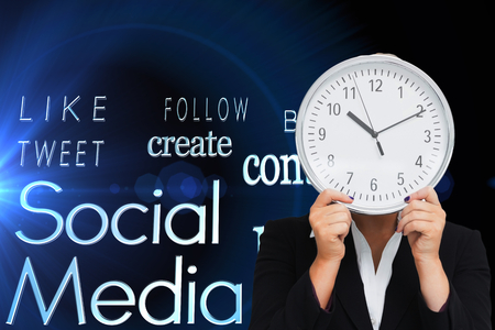 Composite image of businesswoman in suit holding a clock Stock Photo - 27022082