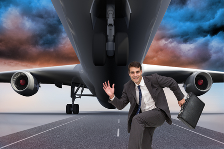 Composite image of happy attractive businessman in a hury photo