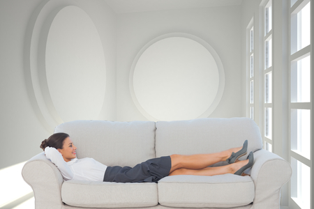 Composite image of smiling business woman lying down on the couch in the office Stock Photo