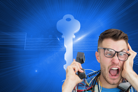 Composite image of portrait of frustrated computer engineer screaming while on call in front of open cpu photo