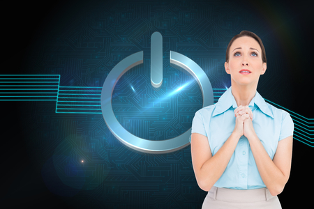 Composite image of troubled young businesswoman praying while posing photo