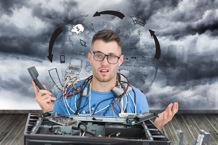 Composite image of confused young it professional with cables and phone in front of open cpu photo