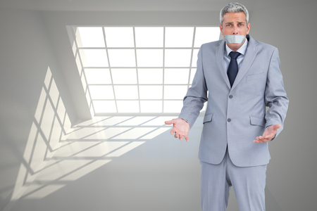 silenced: Composite image of businessman gagged with adhesive tape on mouth Stock Photo