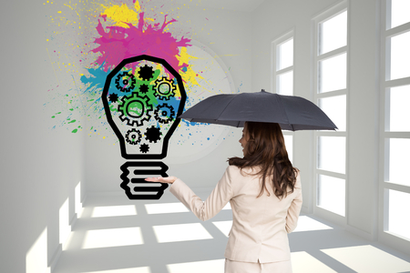 Composite image of elegant businesswoman holding black umbrella photo