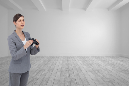 Composite image of curious young businesswoman with binoculars photo