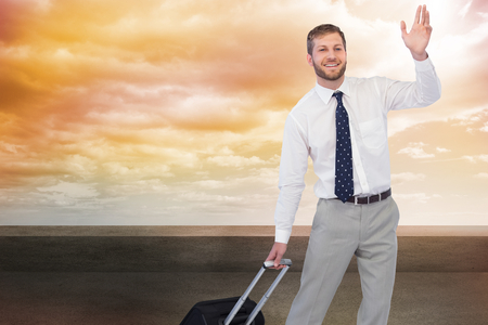 Composite image of handsome businessman with suitcase waving photo