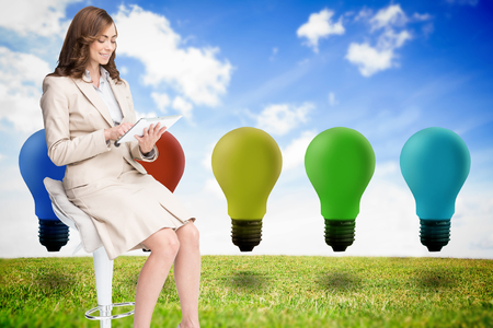 Composite image of happy brunette businesswoman using tablet photo