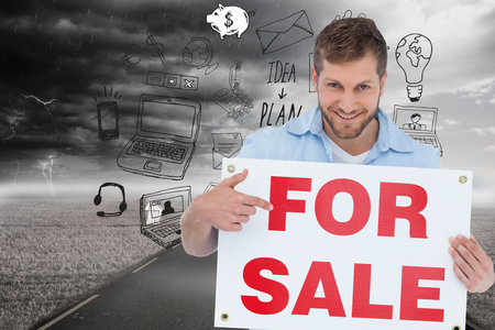 Composite image of smiling model holding a for sale sign photo