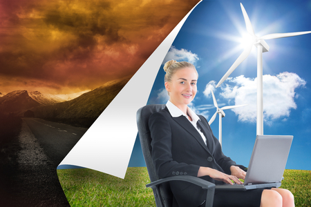 Composite image of attractive blonde businesswoman sitting in swivel chair with laptop photo