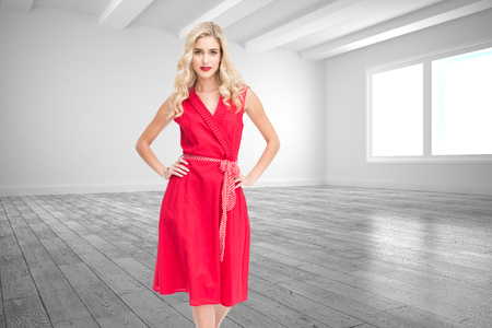 Composite image of elegant blonde standing hands on hips in red dress photo