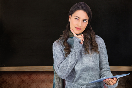 Composite image of pensive model wearing winter clothes holding her tablet photo