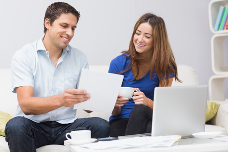 Smiling couple paying their bills online with laptop in living room at home photo