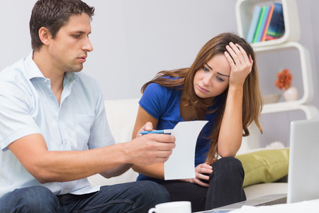 Worried couple paying their bills online with laptop in living room at home photo