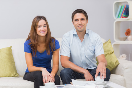 Portrait of a smiling young couple with bills sitting in living room at home photo