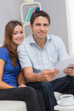 Portrait of a smiling young couple with bills sitting in living room at home Stock Photo - 26993593