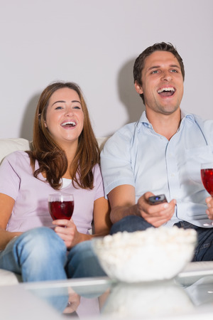 Happy young couple with wine glasses and popcorn enjoying a movie on sofa at home photo