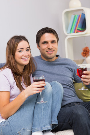 Portrait of a smiling young couple with wine glasses sitting on sofa at home photo