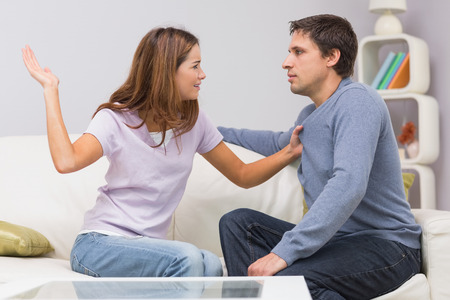Side view of a young woman about to slap man in the living room at home photo
