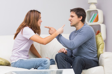 Side view of an angry young couple having an argument in their living room at home photo