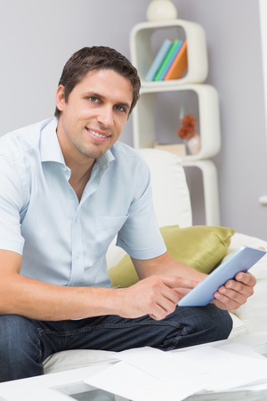 figuring: Portrait of a smiling young man with bills using digital tablet in the living room at home