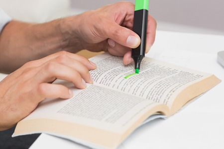 Close-up of a mans hands highlighting text in book on the table