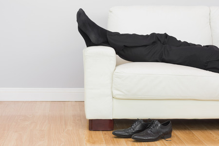 Low section side view of a young businessman resting on sofa in the living room at home