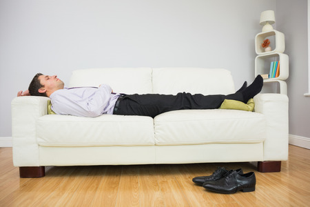 Side view of a tired young businessman sleeping on sofa in the living room at home photo