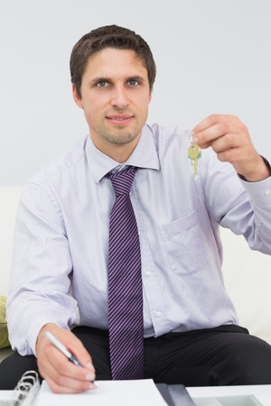 Portrait of a young businessman with documents holding up keys photo