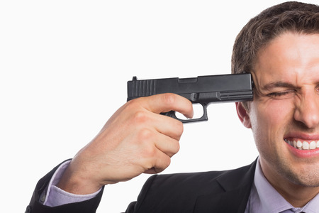 holding gun to head: Close-up of a young businessman holding a gun to head against white background