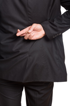 Close-up mid section of a businessman with crossed fingers over white background photo