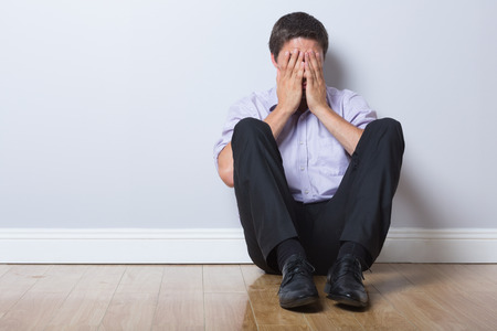 floor covering: Full length of a young businessman sitting on floor with hands covering face in an empty room