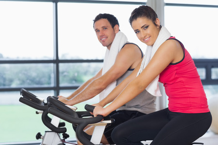 Side view portrait of a young woman and man working out at spinning class in gym photo