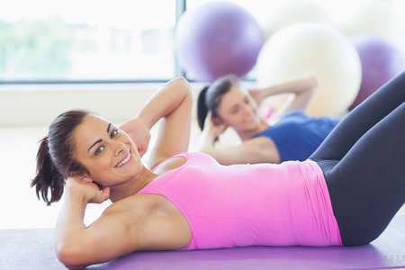 fitness instructor: Two fit young women doing pilate exercises in fitness studio