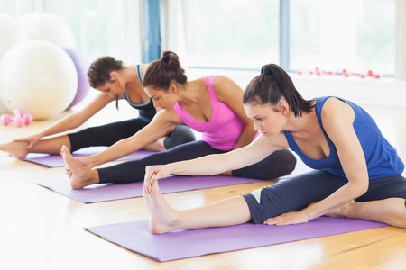 indoors: Fit class stretching legs on mats at yoga class in fitness studio