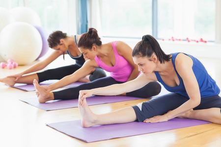 Fit klasse die zich uitstrekt benen op matten op yogales in de fitness-studio Stockfoto - 26993338