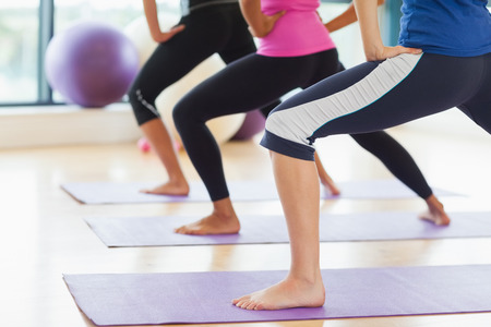 low section: Low section of class and instructor doing stretching pilate exercises in fitness studio