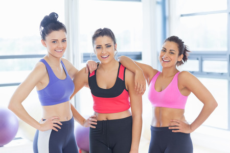 workout gym: Portrait of three fit young women smiling in a bright exercise room Stock Photo