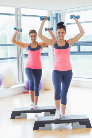 Full length two young women performing step aerobics exercise with dumbbells in a gym photo