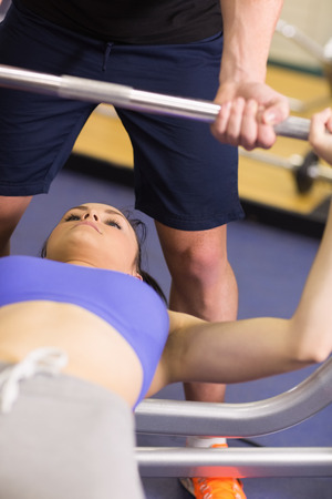 Close-up of a male trainer helping young fit woman to lift the barbell bench press in the gym photo