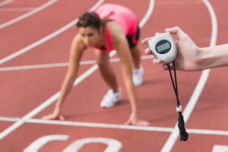Close-up of a hand timing a blurred young womans run on the running track photo