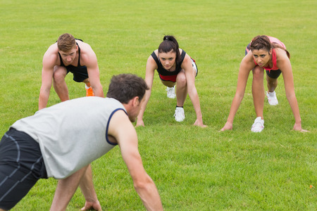 Young people and instructor doing stretching exercise on grass at the park photo