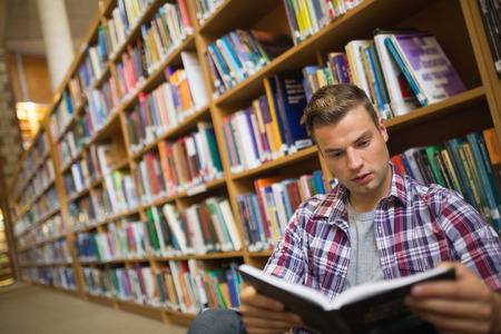 Focused young student sitting on library floor reading book in college photo
