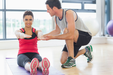Male trainer assisting young woman with pilate exercises in the fitness studio photo