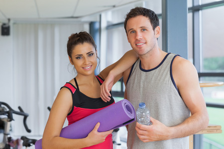 Portrait of a fit young couple with water bottle and exercise mat in a bright exercise room photo