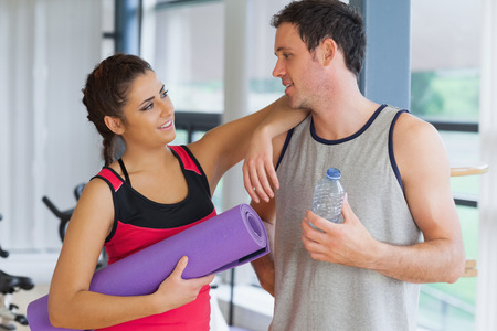 Fit young couple with water bottle and exercise mat in a bright exercise room photo