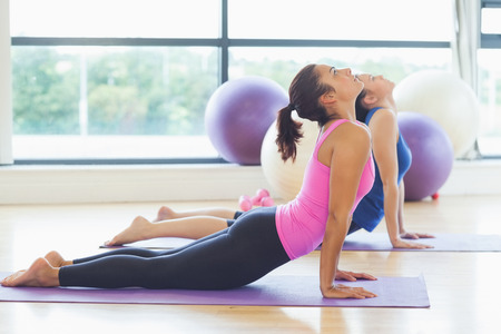 Side view of two fit women doing the cobra pose in a bright fitness studio photo