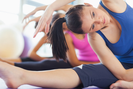 fitness workout: Class and instructor doing stretching pilate exercises in fitness studio Stock Photo