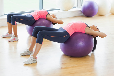 Two fit young women stretching on fitness balls in the bright gym photo
