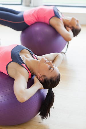 Close-up side view of two fit young women stretching on fitness balls in the bright gym photo